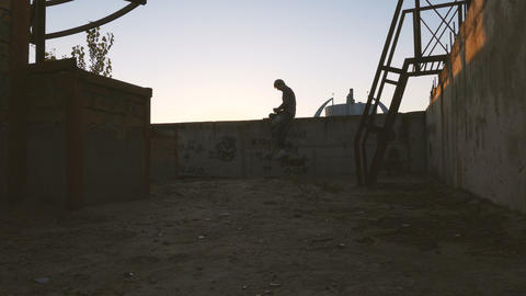 Man listening music at sunset on the roof of skyscaper Archivo