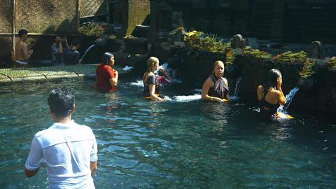 Women take bath at Holy Spring Water Tirta Empul Hindu Temple. Bali. Indonesia Footage