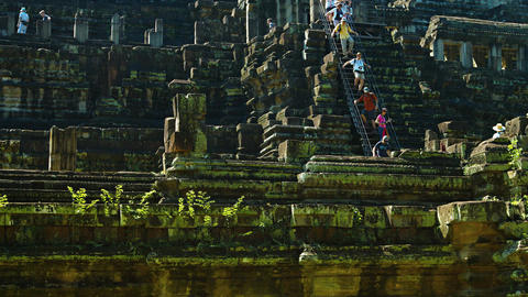 Tourists Clamber down the Steep Stairs of Baphuon Temple. Cambodia. Angkor Live Action