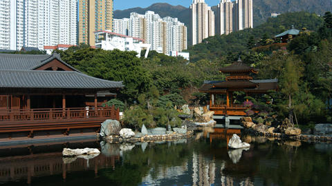 Modern buildings over ornate. wooden buildings of Chi Lin Nunnery in Hong Kong Live Action