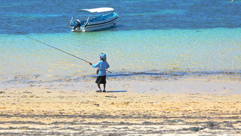 Fisherman with a fishing rod on the public beach. Bali. Indonesia Footage