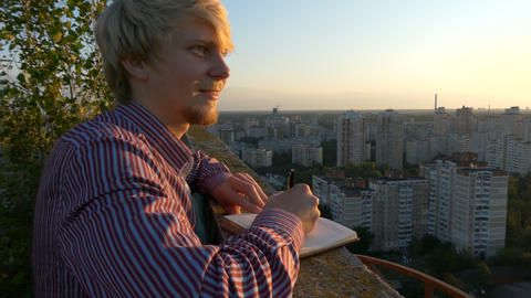4k - Young writer finding his muse on the roof of skyscraper at sunset Image
