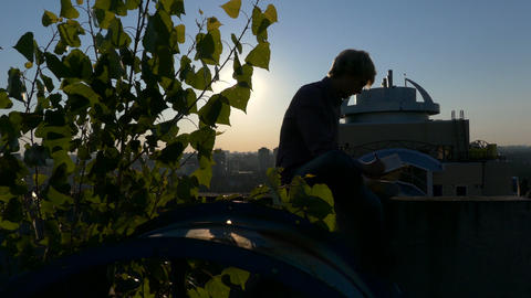 Silhouette of the man that writing norest at sunset on the edge of the roof Footage