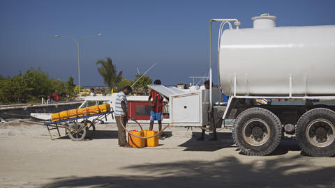 Man sells fuel for boats and motorcycles directly out of tanker truck. Maldives Footage