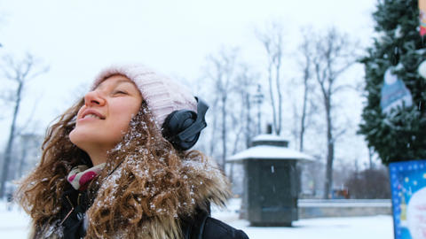 Young cheerful girl catches snowflakes with his mouth in a Park with headphones Footage