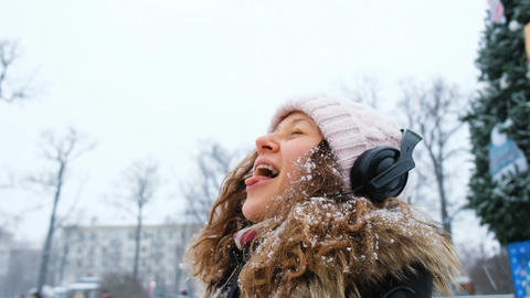 Young girl catching snowflakes with the mouth in a Park with headphones closeup Footage