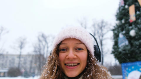 Young caucasian girl catches snowflakes with his mouth in a Park with headphones Footage