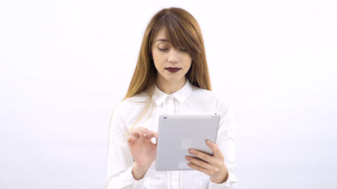 Charming blonde with bangs uses tablet at white background Footage