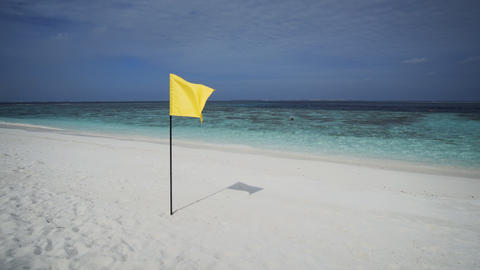 Yellow Flag Flaps over Tropical Beach Paradise in the Maldives Footage