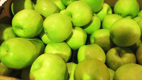 Panoramic shooting of fresh juicy green apples in a plastic container in a Archivo