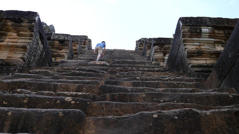 Climbing up a steep stone staircase at Ta Keo temple Footage