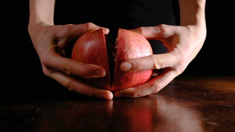 Female hands break the pomegranate in half on a dark background, closeup slow Footage