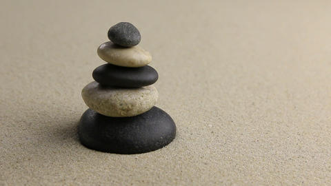 Stones pyramid on sand symbolizing zen Footage