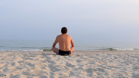 Man meditating at sunset, relaxation, sitting Footage