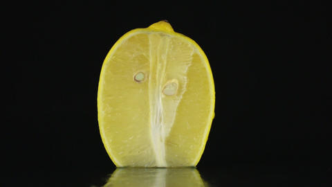 Half of lemon, rotating on a black background Footage