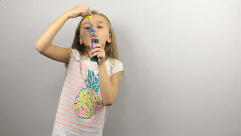 Young girl playing with soap bubbles Footage