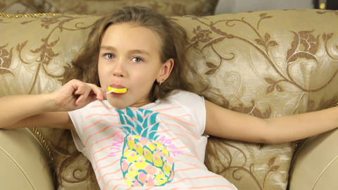 Girl licking candy on a stick in the form of lemon Footage