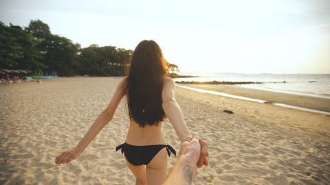 Follow me shot of young sexy girl in a bikini running and holding man hand on Photo