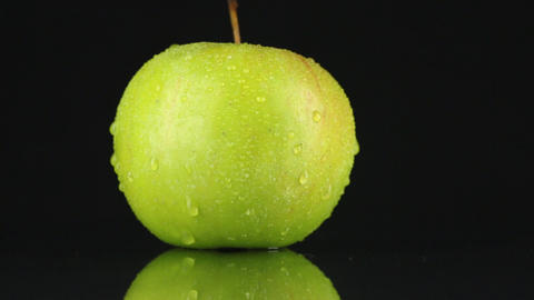 Green apple in drops of dew rotates on its axis Footage
