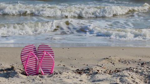 Pink flip flops on yellow sandy beach near sea waves, nobody Filmmaterial