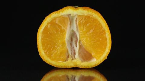 Half of mandarin, rotating on a black background Footage