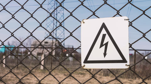 Danger of electric shock. Substation behind the fence. High-voltage wires on the Footage