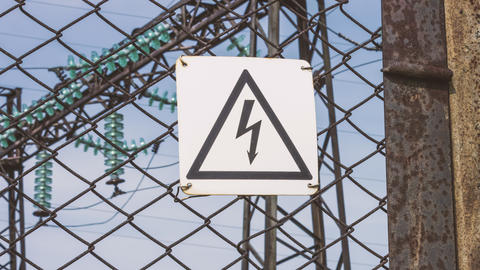 The danger sign of high voltage on the fence of the power plant. Risk of Footage