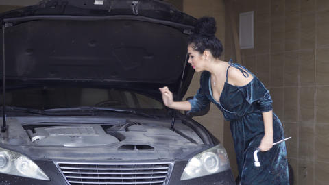 Beautiful woman wearing dress tries to repair her luxury auto with wrenches Footage