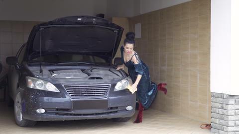 Beautiful woman wearing dress polishes car headlamp with rag Footage
