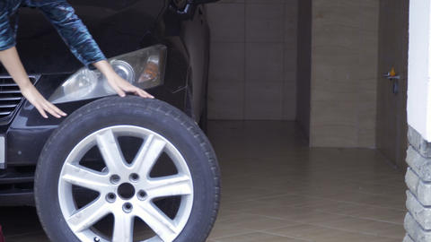 Woman rolls out the car spare wheel Footage