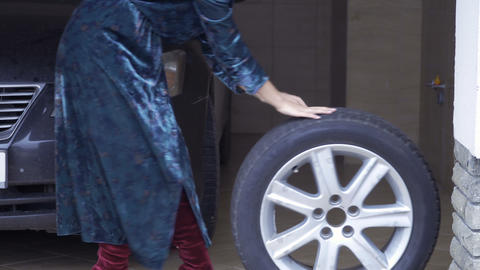 Woman rolls out car spare wheel outside the camera Footage
