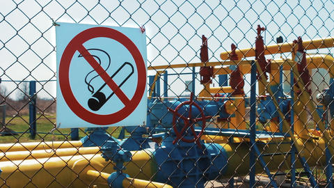 natural gas. Natural gas storage station. no smoking. Warning sign on the fence Live Action