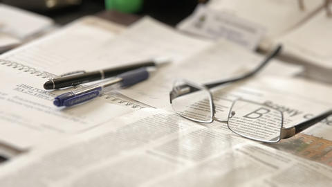 Glasses on a newspaper with a pen Footage