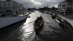 Traditional boats and people on the Central Canal Aveiro Portugal Footage