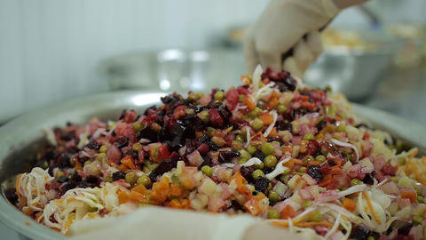 chef hands mixing a tasty salad of colorful vegetables for a vegetarian dish Footage