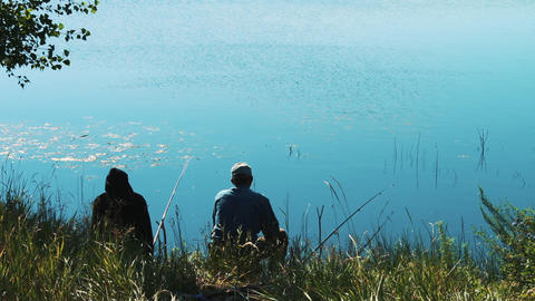 Two fishermen on the shore of the lake are fishing. Fishing rods thrown into the Footage