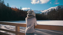 Slender Young Lady is Looking at Mountain Lake in Winter with Sun Lense Flare Footage