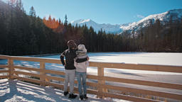 Young Couple is Standing near Mountain Lake in Winter Looking at Landskape Footage