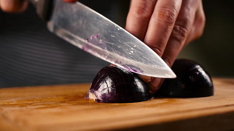 woman hands slicing onions on a wooden cutting board Footage