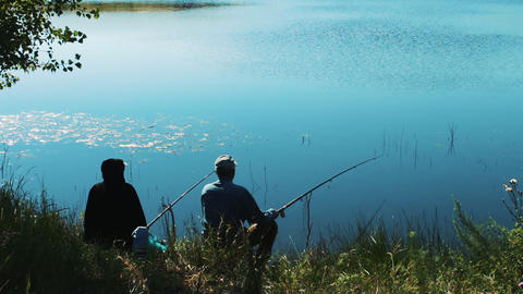 Two fishermen on the shore of the lake are fishing. Morning fishing for fishing Footage