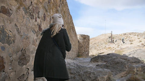 A young woman tourist in a green leather jacket walks alongside the fortress Footage