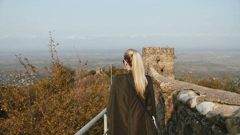 A young woman tourist in a green leather jacket walks the fortress wall of an Footage