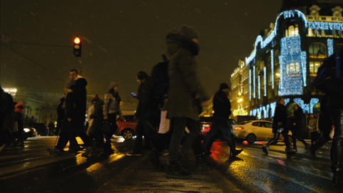 People cross the road on a green traffic light in the snowfall tonight, the city Footage