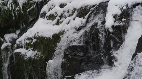 Time lapse of rushing waterfall cascading down icy rocks Footage