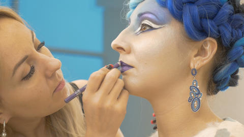 The make-up artist draws the model's lips in purple. Creates a magical image Footage