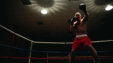 Professional punched fighter in a boxing ring in red sherds and boxing gloves Footage