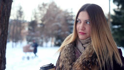 Portrait. Beautiful young girl drinks coffee having a good mood in winter in the Footage