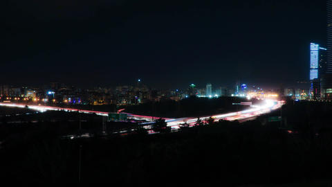 Cityscape timelapse at night. Busy traffic across the main road at rush hour Image