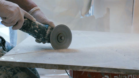 Worker cutting a tile using an angle grinder at construction site Footage