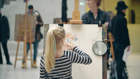 AMSTERDAM, NETHERLANDS - DECEMBER 26, 2017. Girl drawing her mom's portrait Footage